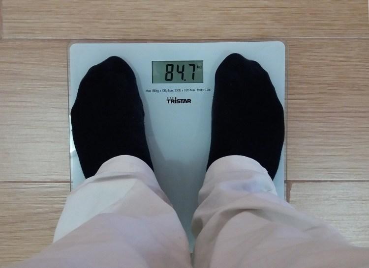 Imagen de un hombre comprobando su peso en una báscula
