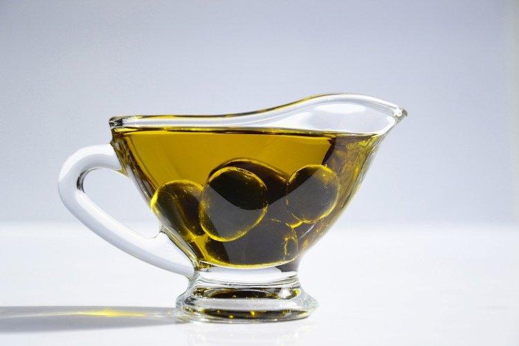 un cuenco que contiene aceitunas en aceite de oliva, un alimento importante para una dieta de aumento de masa