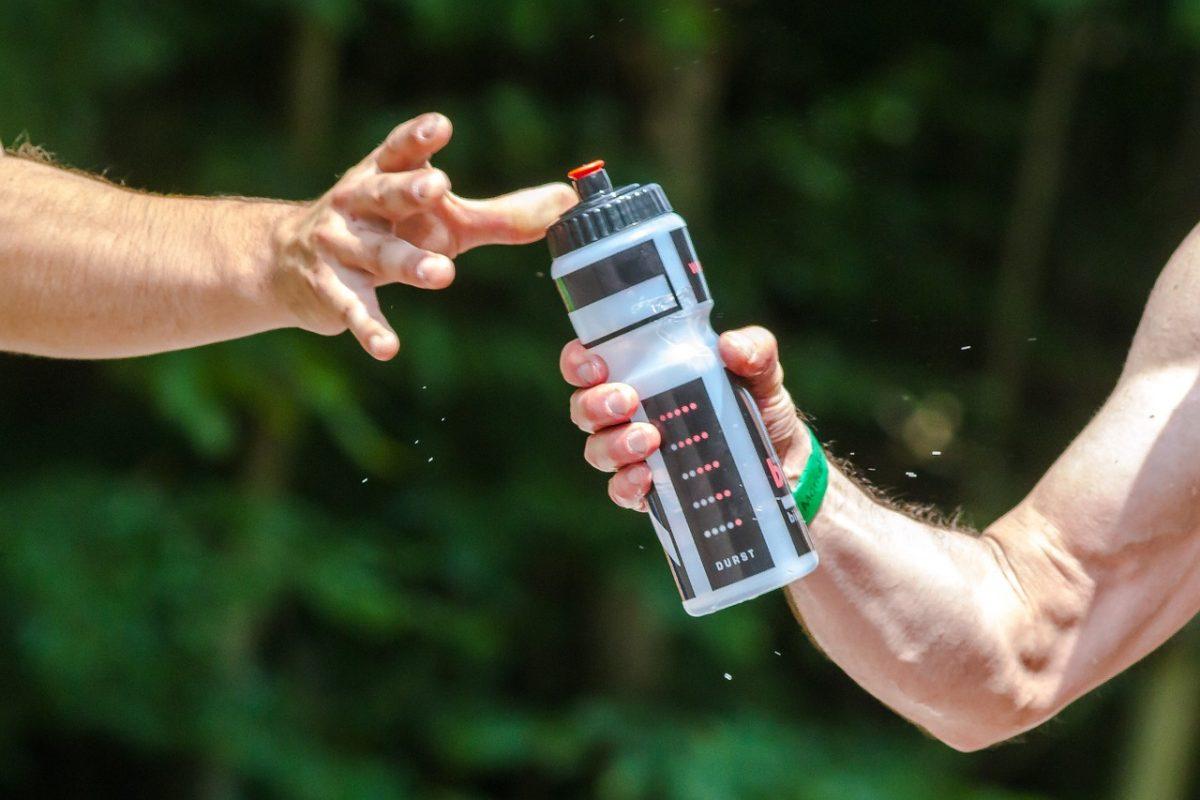 deportistas dando una bebida de ejercicio a otro deportista